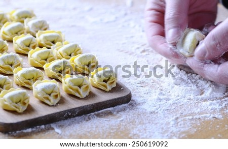 Preparing homemade tortellini on wooden table in the kitchen.  - stock photo