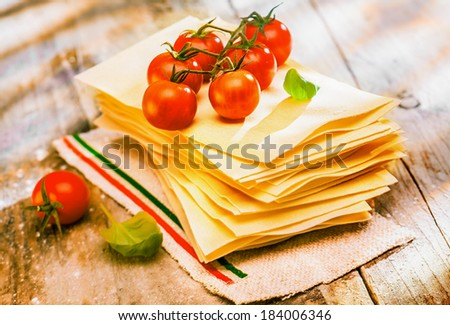 Preparing Italian lasagne with fresh ripe red cherry tomatoes and basil on sheets of dried pasta standing ready on an old rustic wooden kitchen table - stock photo