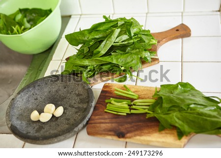 Preparing Japanese spinach to be cooked in the kitchen - stock photo