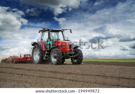 Preparing land for sowing at spring, farmer in tractor - stock photo