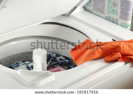 Preparing laundry for washing in machine - stock photo