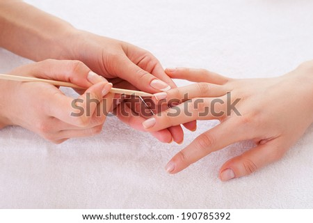 Preparing nails for manicure. Close-up of manicure master preparing customers nails for manicure - stock photo