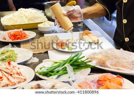 Preparing of traditional Japanese sushi rolls with salmon, cook adds sauce on plate. Selective focus - stock photo