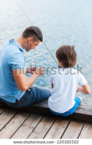Preparing rod for fishing. Rear view of father and son sitting at the quayside and preparing fishing rod for fishing  - stock photo