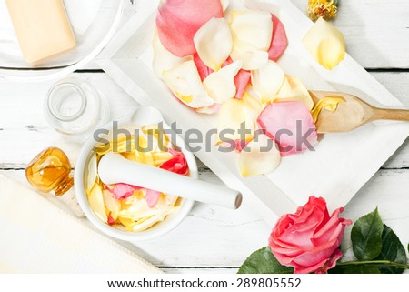 Preparing rose petals for aromatic essences in a mortar - stock photo