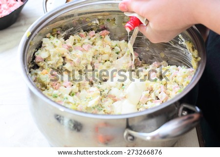 Preparing russian traditional salad Olivier, mix ingredients - stock photo