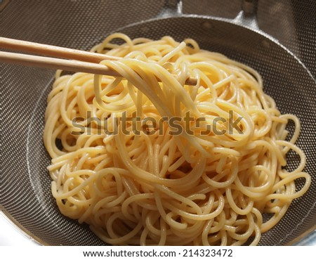 Preparing Spaghetti on colander - stock photo