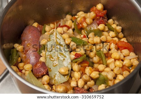 "Preparing spanish ""cocido"" stew with chickpeas, sausages, tomato and peppers. - stock photo"