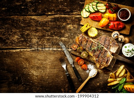 Preparing t-bone steak and roast vegetables in a country kitchen with bell peppers, mushrooms, tomato, potato, mangetout peas, and corn on a rustic wooden table with copyspace - stock photo