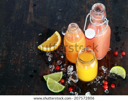 Preparing tasty healthy summer fruit juices in glass bottles with slices of fresh orange, lemon, lime and cranberries, viewed high angle on a dark rustic wooden surface with copyspace - stock photo