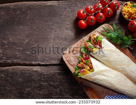 Preparing tasty Tex-Mex tortilla wraps in a rustic kitchen filled with fresh salad ingredients, corn kernels, herbs and diced meat , overhead view with ingredients and copyspace - stock photo