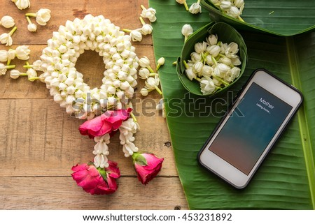 Preparing Thai traditional jasmine garland. symbol of Mothers day in Thailand. and calling to mother by mobile phone. - stock photo