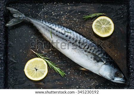 Preparing to bake mackerel with lemon and spices on an old scratched iron pan - stock photo