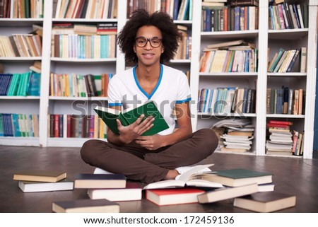Preparing to exams. Cheerful African teenager reading a book and smiling while sitting on the floor at the library - stock photo