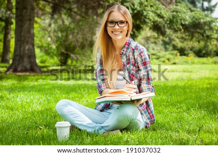 Preparing to exams outdoors. Beautiful young female student writing something in note pad while sitting in a park - stock photo