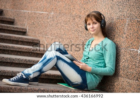 Preparing to exams outdoors. Headphones music. Beautiful young female student writing or reading something from note pad. Woman sitting on stairs in city park.