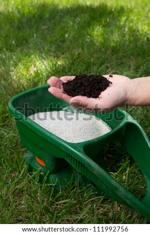 Preparing to fertilize lawn in back yard in spring time