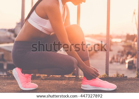 Preparing to run. Close-up of beautiful young woman in sports clothing tying her shoelaces while standing on the bridge with evening sunlight and urban view in the background - stock photo