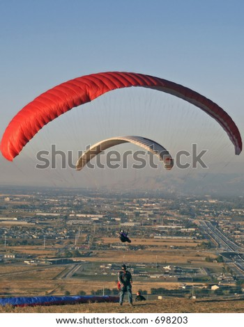 Preparing to take off with red parasail and flying white parasail over the Salt Lake Valley, Utah - stock photo