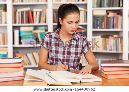 Preparing to the exams. Thoughtful young woman writing something in her note pad and reading book while sitting at the library desk - stock photo