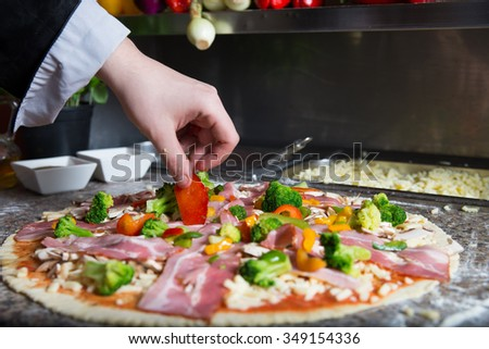Preparing traditional pizza in professional pizzeria. Chef is covered pastry by tomato sauce, mozzarella cheese, mushrooms, bacon and fresh vegetables like pepper and broccoli.