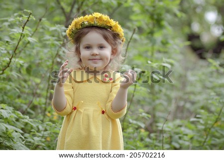 Preschool age girl with a wreath of yellow flowers in a yellow dress