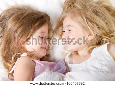 Preschool age girls in bed having a sleep-over - stock photo