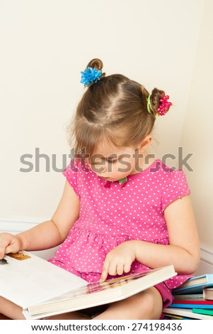 preschool age little girl reading a book - stock photo