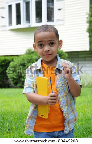 Preschool Boy Eyebrows Raised holding Paint brush Set Wearing Orange Plaid