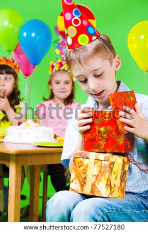 Preschool boy in party hat looking into present box - stock photo