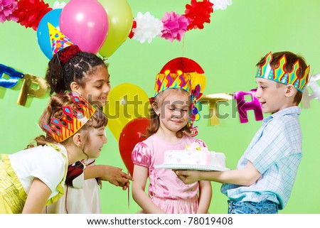 Preschool boy offering birthday cake to his guests - stock photo