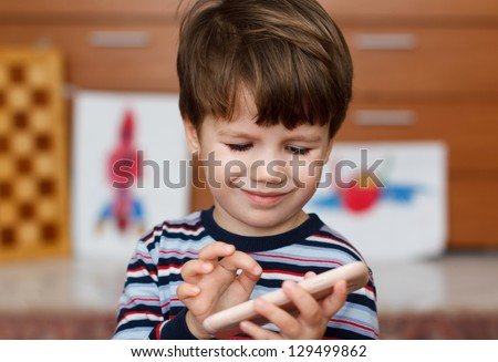 Preschool boy playing on smartphone - stock photo