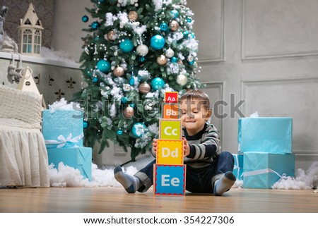 Preschool boy playing with wooden alphabet blocks against Christmas tree - stock photo
