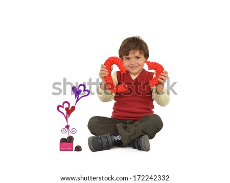 Preschool Child Holding Broken Heart Smiling sitting next to chocolate bonbons with Te Amo (I Love You in Castellano Spanish) isolated on white background - stock photo
