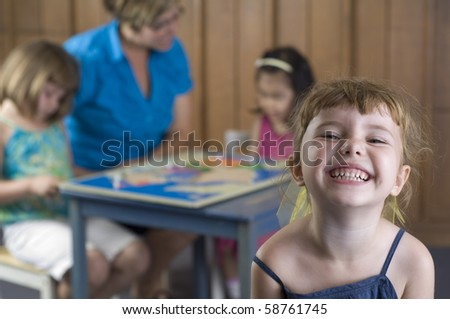 Preschool children and teacher play and learn geography by using a puzzle map. - stock photo