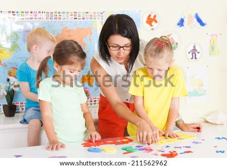 Preschool children in the classroom with a teacher - stock photo