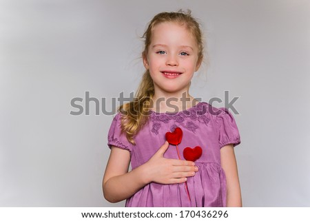 Preschool cute girl with strawberry blonde hairs and lilac dress who holds two red heart pattern on the chest against the light grey background