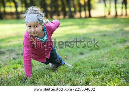 Preschool girl making push-ups exercises with one hand on green grass - stock photo