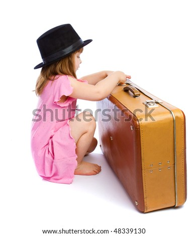 Preschool girl unlocking an old suitcase, isolated - stock photo