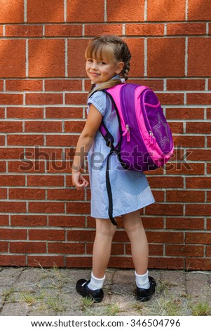 Preschool girl with braids dressed in school uniform gingham blue dress and black classic shoes standing near the school wall with her backpack. Back to school.  - stock photo