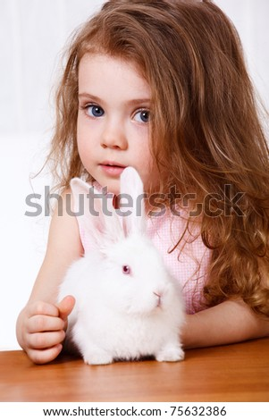 Preschool girl with long hair and a white rabbit sitting on the table - stock photo