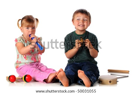 Preschool siblings playing a recorder and rhythm instruments together.  Isolated on white. - stock photo