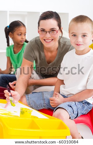 preschool teacher and kids in classroom - stock photo