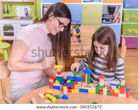 Preschool Teacher Supporting Girls Creativity - stock photo