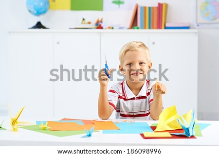 Preschooler boy making colorful origami - stock photo