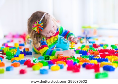 Preschooler child playing with colorful toy blocks. Kids play with educational toys at kindergarten or day care. Preschool children build tower with plastic block. Toddler kid in nursery. - stock photo