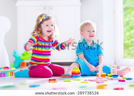 Preschooler child playing with colorful toy blocks. Kids play with educational wooden toys at kindergarten or day care. Preschool children build tower with wood block. Toddler kid in nursery. - stock photo