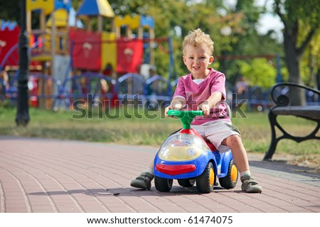 Preschooler driving his toy vehicle in the park - stock photo