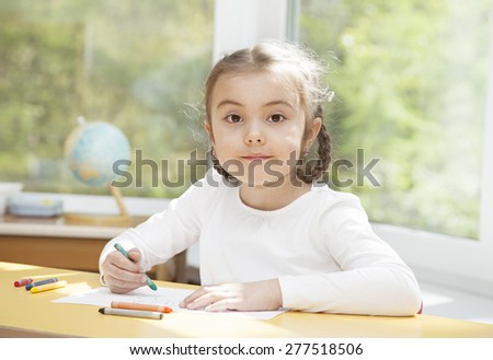 Preschooler girl drawing with pencils sitting at the table in the nursery