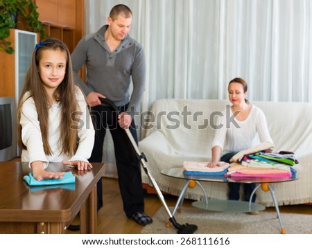 Preschooler girl helping parents to clean at home. Focus on girl - stock photo